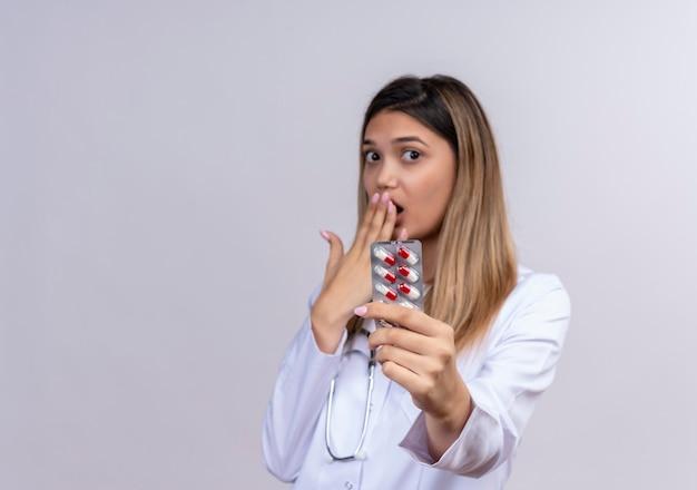 Jonge mooie vrouw arts die witte laag met de blaar van de stethoscoopholding met pillen draagt die verbaasd verbaasd kijken die mond met hand behandelt