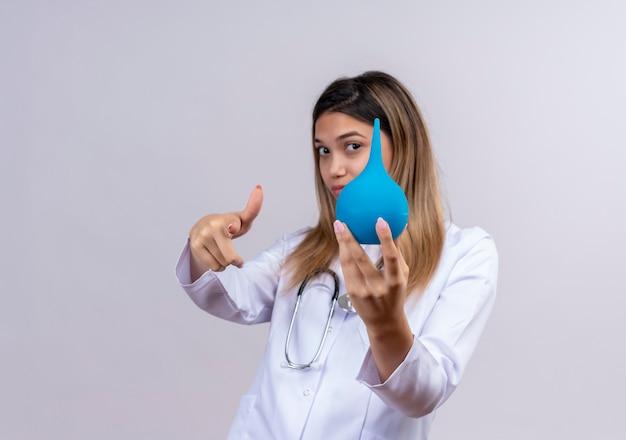 Jonge mooie vrouw arts die witte laag met stethoscoop draagt die een klysma toont die met wijsvinger naar voorzijde richt
