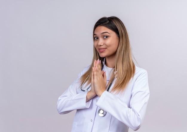 Jonge mooie vrouw arts dragen witte jas met stethoscoop houden hand in gebed namaste gebaar dankbaar en gelukkig voelen