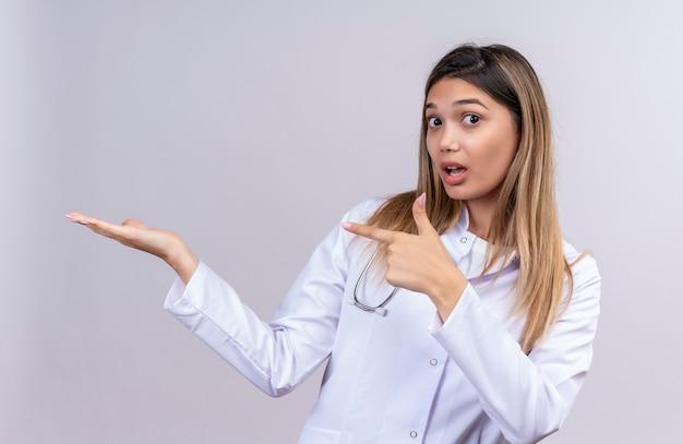 Jonge mooie vrouw arts dragen witte jas met stethoscoop presenteren met haar arm van haar hand en wijzend met de vinger naar de kant op zoek verrast