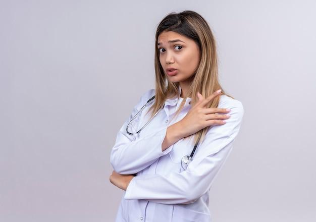 Jonge mooie vrouw arts dragen witte jas met stethoscoop staan met gekruiste armen op zoek bezorgd