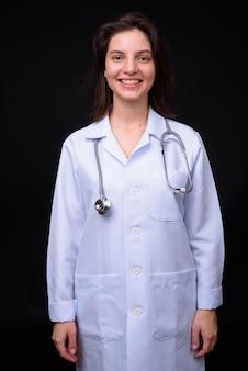 Jonge mooie vrouw arts tegen zwarte muur