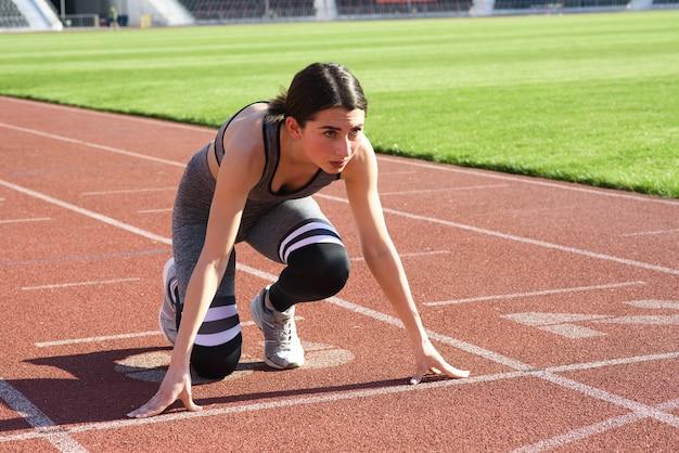 Jonge mooie vrouw atleet buiten staande in start pose in het stadion