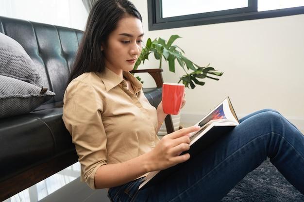 Jonge mooie vrouw aziatische witte huid zitten drinken koffie en het lezen van een boek geniet van rust