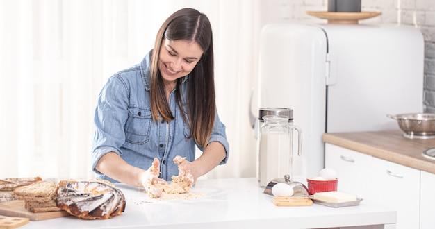 Jonge mooie vrouw bereidt zelfgemaakte taarten in de keuken.