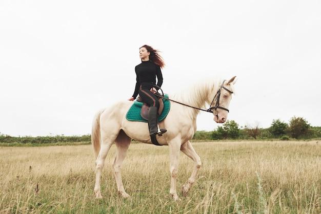 Jonge mooie vrouw - berijden van een paard, paardensport in het voorjaar