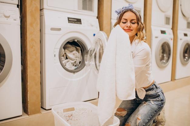Jonge mooie vrouw bij een wasserette