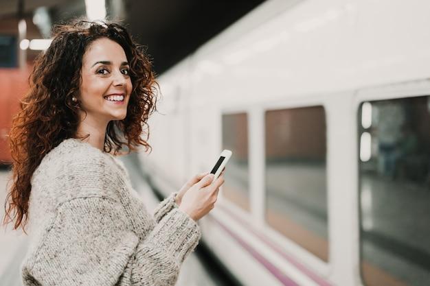 Jonge mooie vrouw bij station die mobiele telefoon met behulp van alvorens een trein te halen. reizen, technologie