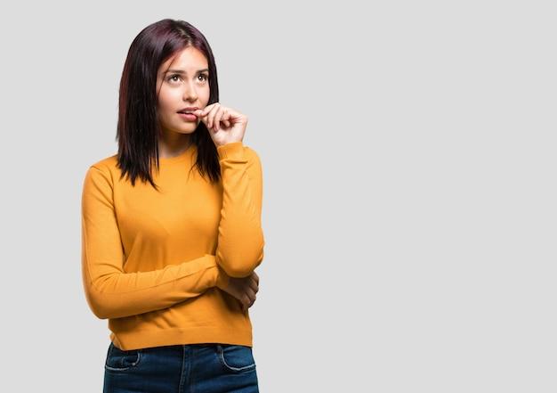 Jonge mooie vrouw bijt nagels, nerveus en erg angstig en bang voor de toekomst, voelt paniek en stress