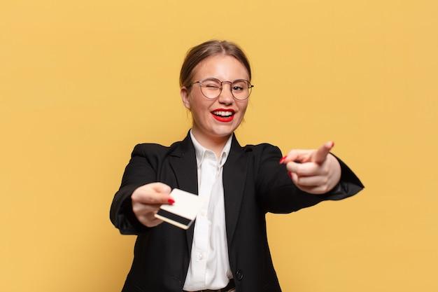 Jonge mooie vrouw blij en verrast uitdrukking creditcard concept