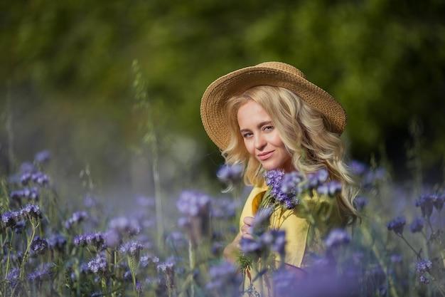 Jonge mooie vrouw blonde in een hoed loopt door een veld met paarse bloemen. zomer. voorjaar.