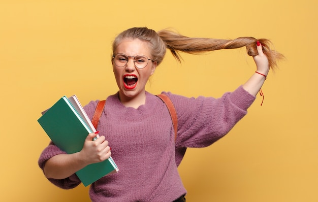 Jonge mooie vrouw boos en verveeld expressie. studentenconcept