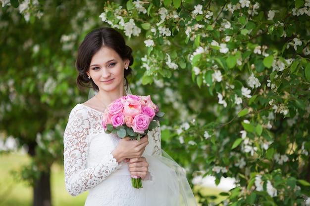 Jonge mooie vrouw, bruid met huwelijksboeket in bloeiende tuin