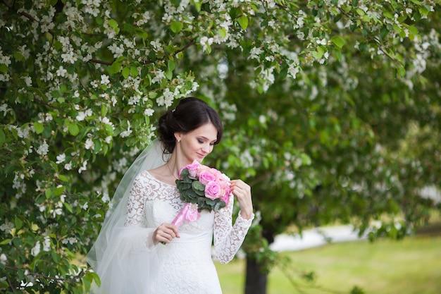 Jonge mooie vrouw, bruid met roze huwelijksboeket in bloeiende tuin
