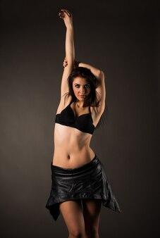 Jonge mooie vrouw brunette in lederen rok en zwarte beha poseren op een grijze achtergrond. ondergoed reclame concept. advertentie ruimte