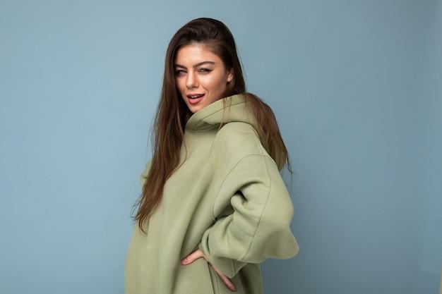 Jonge mooie vrouw camera kijken. trendy meisje in casual hipster hoodie kleding. positieve vrouw toont gezichtsemoties. grappig model geïsoleerd op blauwe achtergrond met vrije ruimte voor tekst