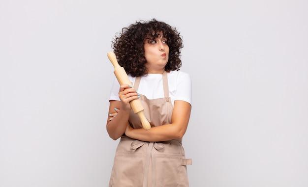 Jonge mooie vrouw chef-kok schouderophalend, verward en onzeker gevoel, twijfelende met gekruiste armen en verbaasde blik