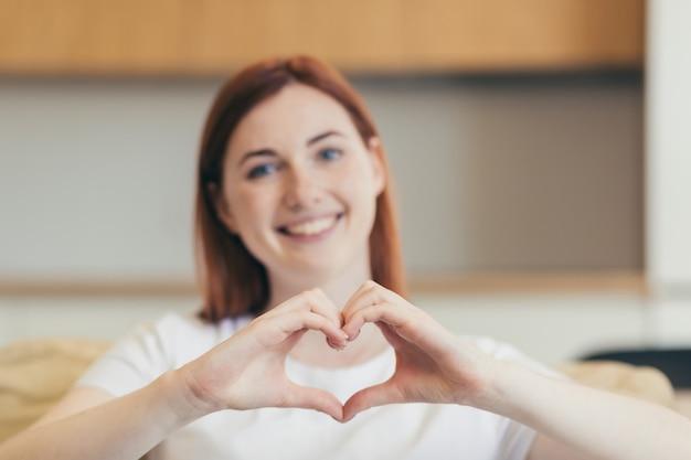 Jonge mooie vrouw communiceert via video om thuis op de bank te zitten, met een hartteken met handen