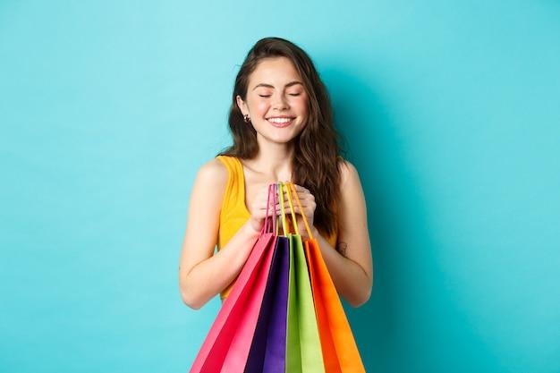 Jonge mooie vrouw dagdromen over het dragen van nieuwe kleding, boodschappentassen vasthouden, ogen sluiten en dromerig glimlachen, staande over blauwe achtergrond.