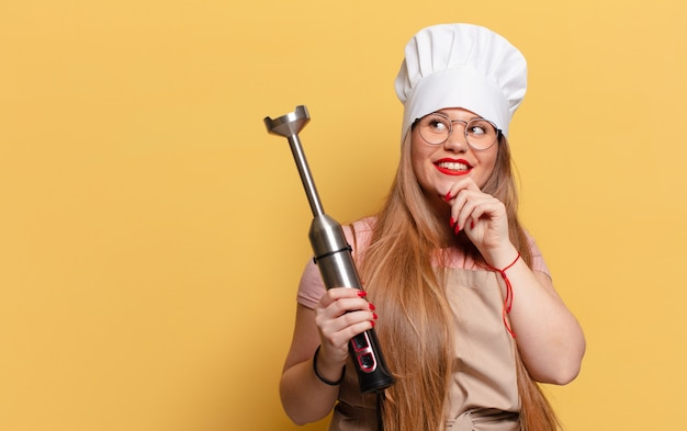 Jonge mooie vrouw. denken of twijfelen expressie chef concept