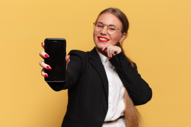 Jonge mooie vrouw. denken of twijfelen expressie slimme telefoon concept