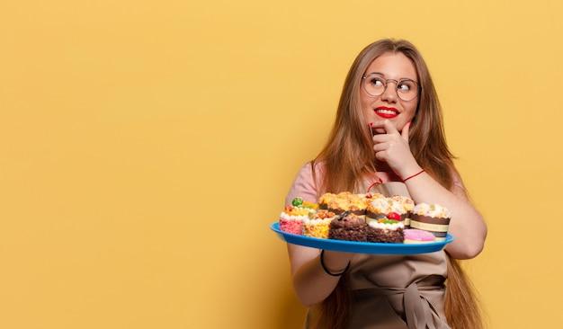 Jonge mooie vrouw. denkende of twijfelende uitdrukking bakker met cupcakes