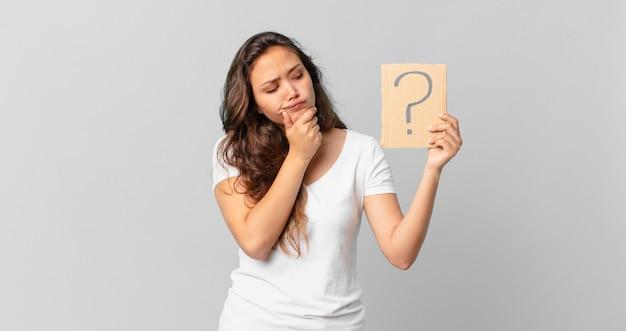 Jonge mooie vrouw denkt, voelt zich twijfelachtig en verward en houdt een vraagteken vast