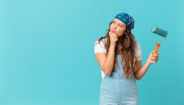 Jonge mooie vrouw denkt, voelt zich twijfelachtig en verward en schildert een muur