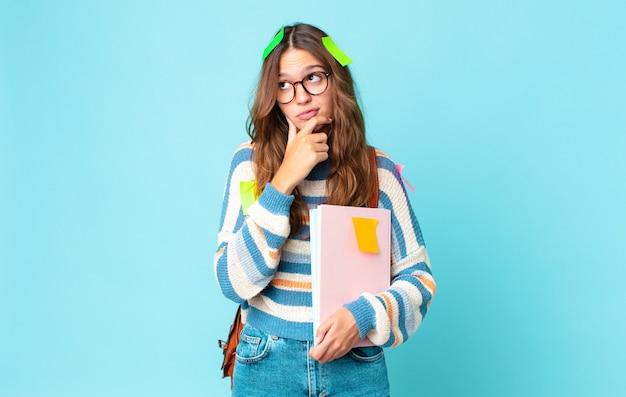 Jonge mooie vrouw denkt, voelt zich twijfelachtig en verward met een tas en houdt boeken vast