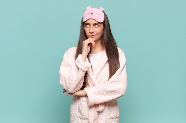 Jonge mooie vrouw denkt, voelt zich twijfelachtig en verward, met verschillende opties, zich afvragend welke beslissing ze moet nemen. wakker worden met pyjama's concept