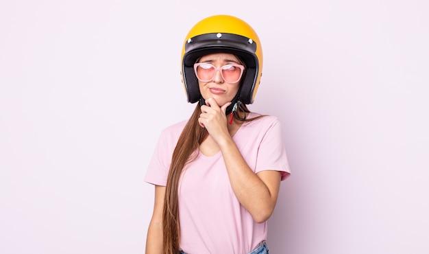 Jonge mooie vrouw denkt, voelt zich twijfelachtig en verward. motorrijder en helm