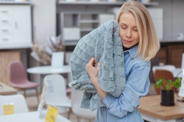 Jonge mooie vrouw die aan een zachte deken knuffelen, winkelend voor huisgoederen bij meubilairopslag