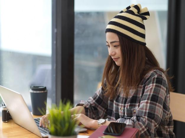 Jonge mooie vrouw die aan haar project werkt tijdens het gebruik van tabletcomputer in comfortabele werkruimte