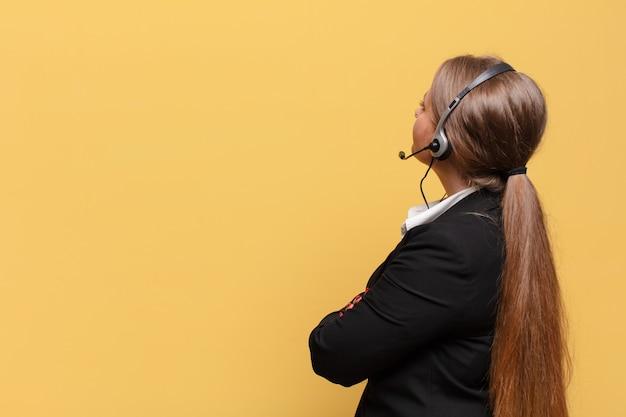 Jonge mooie vrouw die aan telemarketeerconcept denkt of twijfelt