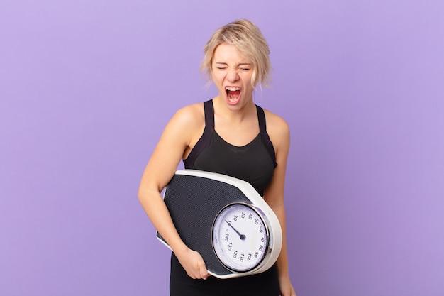 Jonge mooie vrouw die agressief schreeuwt en er erg boos uitziet. dieet concept