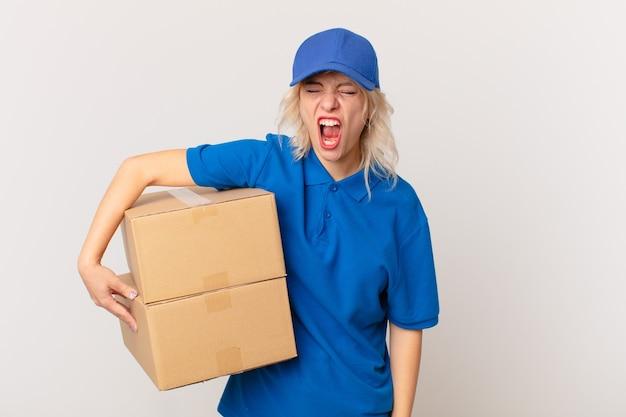 Jonge mooie vrouw die agressief schreeuwt en er erg boos uitziet. pakket leveren concept