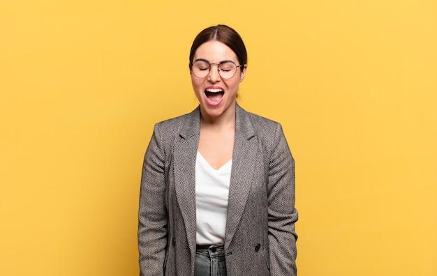 Jonge mooie vrouw die agressief schreeuwt, er erg boos, gefrustreerd, verontwaardigd of geïrriteerd uitziet, nee schreeuwt