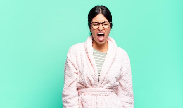 Jonge mooie vrouw die agressief schreeuwt, erg boos, gefrustreerd, verontwaardigd of geïrriteerd kijkt, nee schreeuwt. pyjama's concept