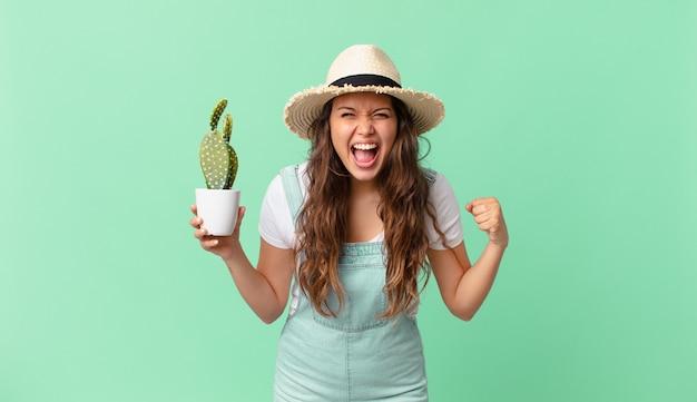 Jonge mooie vrouw die agressief schreeuwt met een boze uitdrukking en een cactus vasthoudt