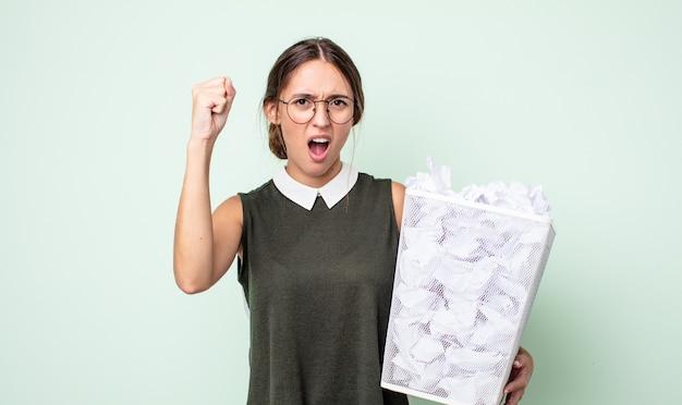 Jonge mooie vrouw die agressief schreeuwt met een boze uitdrukking. papier ballen prullenbak concept