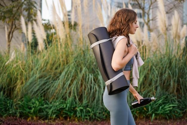 Jonge mooie vrouw die alleen loopt in het stadspark na haar yoga-fitnessles