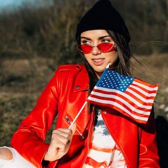 Jonge mooie vrouw die amerikaanse vlag houdt
