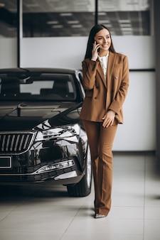 Jonge mooie vrouw die auto in een autotoonzaal kiest