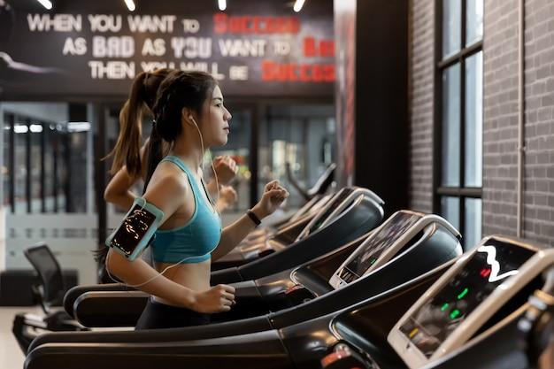 Jonge mooie vrouw die aziatisch op een tredmolen bij gymnastiek loopt.