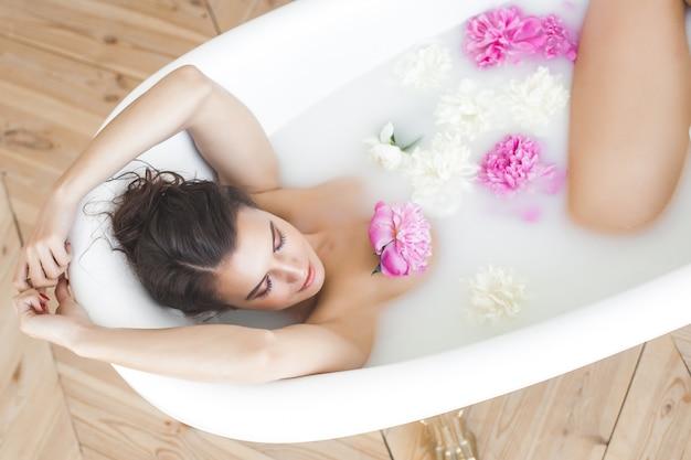 Jonge mooie vrouw die bad met bloemen en melk neemt