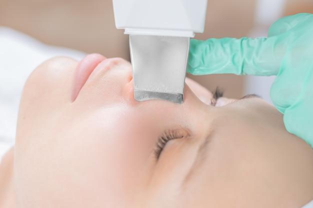 Jonge mooie vrouw die behandelingen in schoonheidssalons ontvangt. ultrasone reinigingsprocedure. hardware cosmetologie. gemengde media