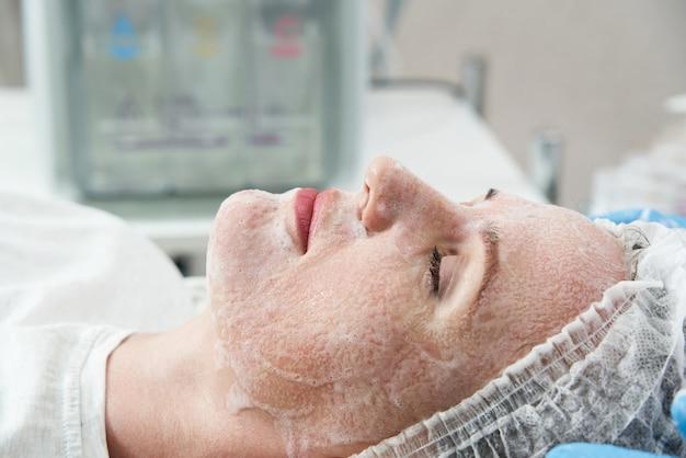 Jonge mooie vrouw die behandelingen krijgt in schoonheidssalons met gezichtsreinigingsschuim