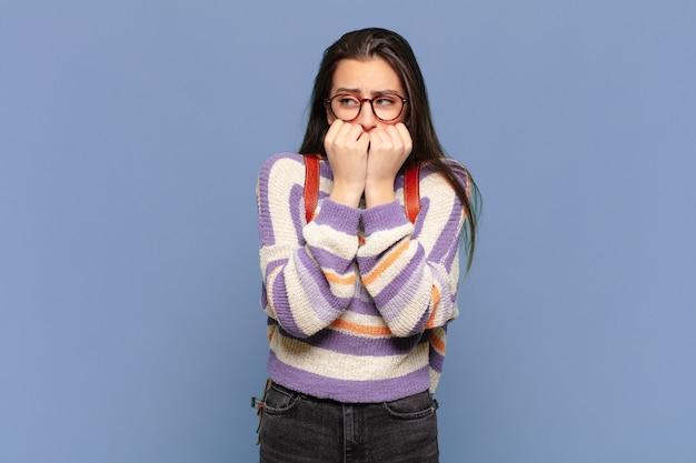 Jonge mooie vrouw die bezorgd, angstig, gestrest en bang kijkt, vingernagels bijt en op zoek is naar laterale kopieerruimte. studentenconcept