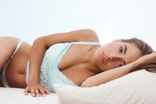 Jonge mooie vrouw die bij bed vroeg het ontwaken in ochtend liggen