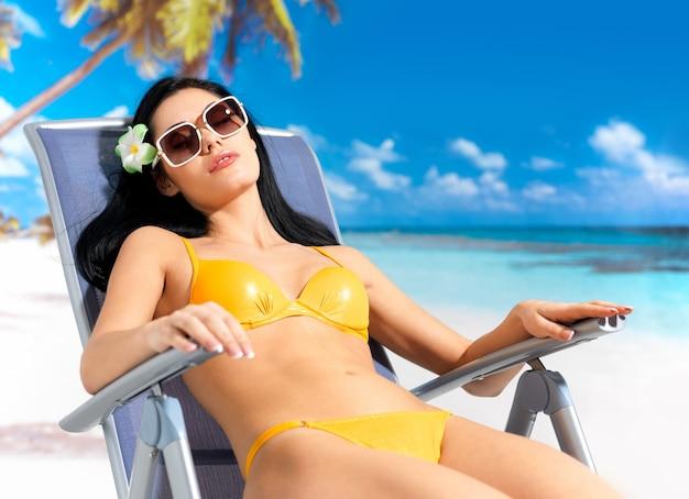 Jonge mooie vrouw die bij strand geniet van.